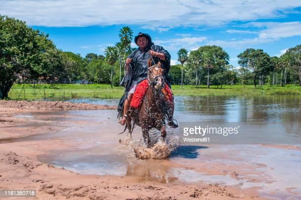 local man riding through the unesco world heritage, pantanal, brazil - pantanal wetlands stock pictures, royalty-free photos & images