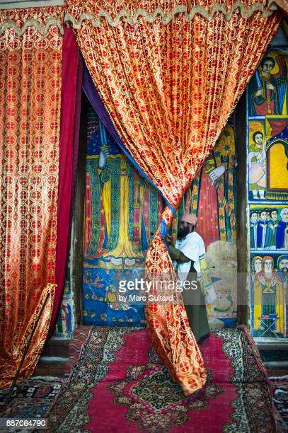 a local man rolling back a curtain to unveil old religious paintings to show tourists inside of the church of our lady mary of zion, axum, ethiopia - ark of the covenant stock pictures, royalty-free photos & images