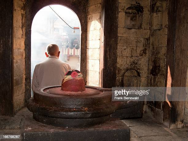 Local man sits behind a Shiva Lingam to watch cremation ceremony at Pashupatinath temple. .