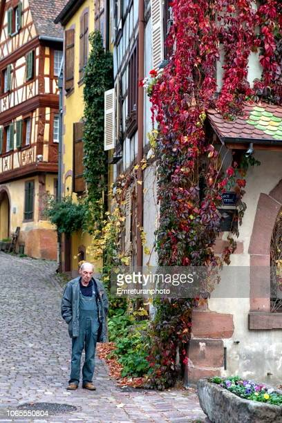 a local man standing at the street in kayserberg village,alsace region. - emreturanphoto stock pictures, royalty-free photos & images