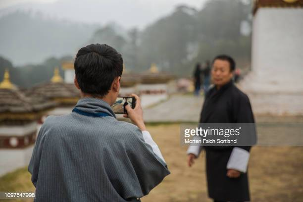 a local man takes a photo using a smartphone at the chortens of the dochula mountain pass in dochula, bhutan springtime - dochula pass stock-fotos und bilder