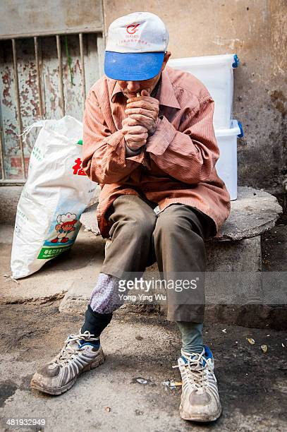 Local man takes a smoke break. Two colour socks, two boxes, two bottle caps, a bag.