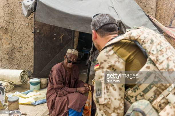 A Local man talk to soldiers of the Bundeswehr the German Armed Forces at the Castor military camp in Gao Mali 19 May 2017 Members of the German...