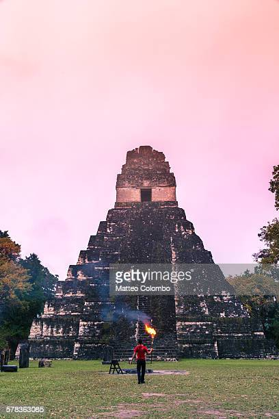 Local man with a torch in front of temple I, Tikal
