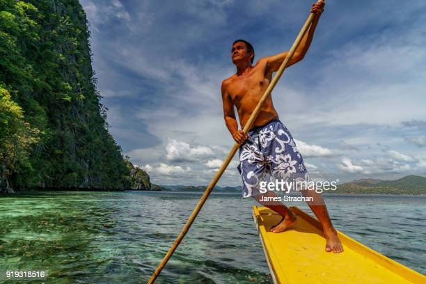 local man with long pole punts his way across lake coron standing at the back of a canoe, coron island, philippines (model release) - james strachan stock pictures, royalty-free photos & images