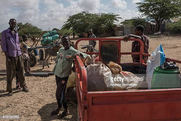 Local men and boys gather at a water filling station just outside the African Union Mission in Somalia's Forward Operating Base Barawe on October 11...