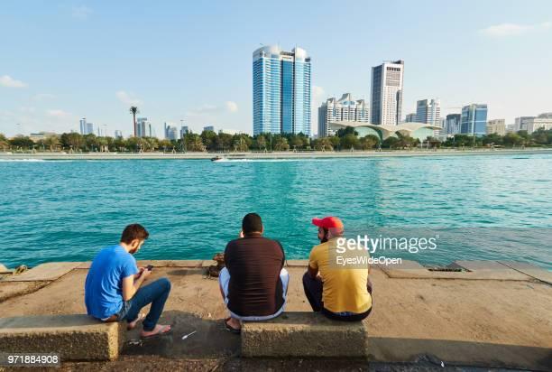 Local men are sitting on Saadiyat Island and looking to skyscrapers on November 27 2015 in Abu Dhabi Emirate Abu Dhabi
