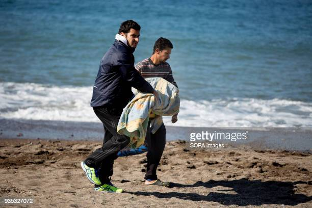 Local men carry the body of a drowned child who washed ashore at after a boat carrying asylumseekers capsized in the Aegean Sea attempting to reach...