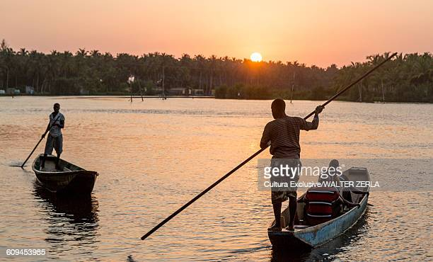 local men crossing river in water taxi punt at sunset, abidjan, ivory coast, africa - abidjan stock pictures, royalty-free photos & images