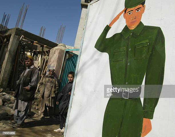 Local men look over at a painting of an Afghan soldier outside the venue for the inauguration ceremony of a USled Provincial Reconstruction Team...