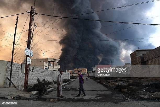 Local men pause as an oil field that was set on fire by retreating ISIS fighters ahead of the Mosul offensive burns behind him on October 21 2016 in...