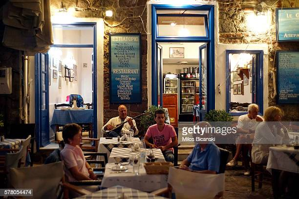Local men play music in a quiet taverna in Molivos town on 18 July 2016 on Lesvos island Greece The increase in refugees arriving on the island of...