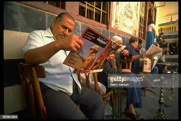 Local men relaxing al fresco at coffeehouse puffing on water pipes chatting reading newspapers mag w cover pic of gulf crisis soldier