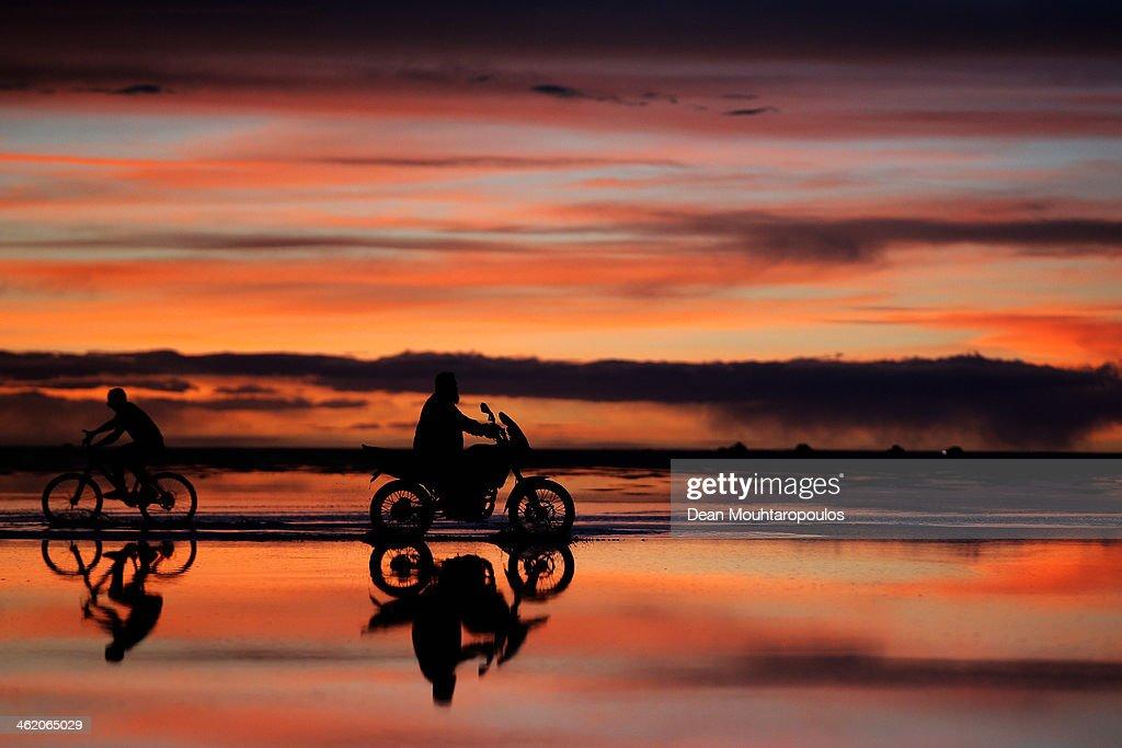 Local men ride their motorbike and bicycle as the sun sets over the Salar de Uyuni of Uyuni Salt Flat during Day 7 of the 2014 Dakar Rally on January 11, 2014 in Uyuni, Bolivia.