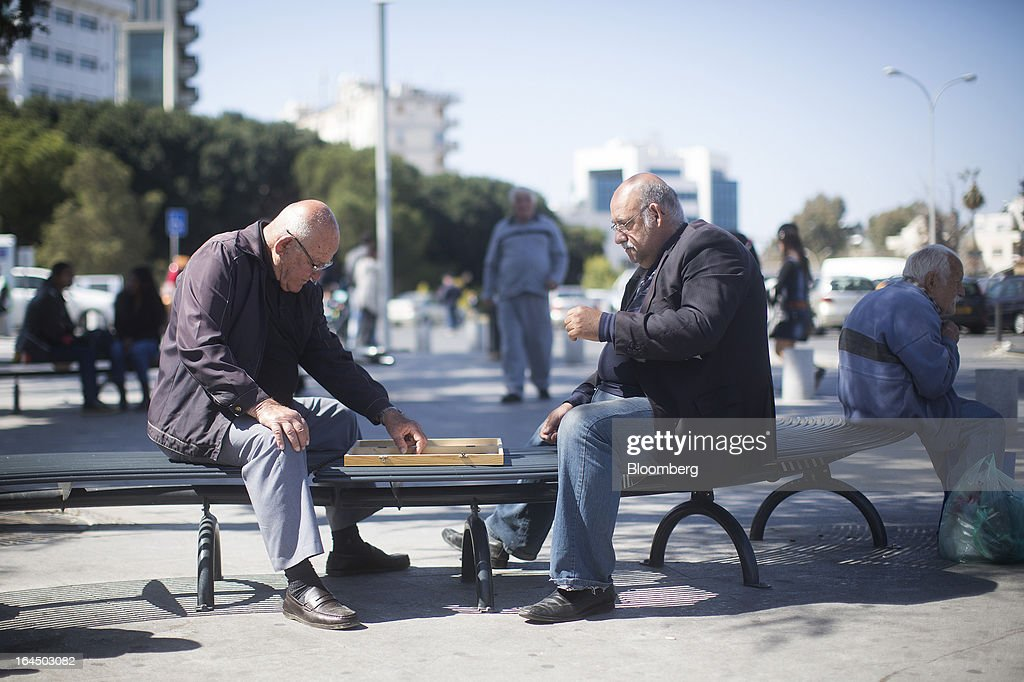 Local men sit and play backgammon on a street bench in Nicosia, Cyprus, on Sunday, March 24, 2013. Cyprus's fate hangs in the balance as euro-area finance ministers meet today to decide whether the tiny Mediterranean island has done enough for a bailout that will avert its financial collapse. Photographer: Simon Dawson/Bloomberg via Getty Images