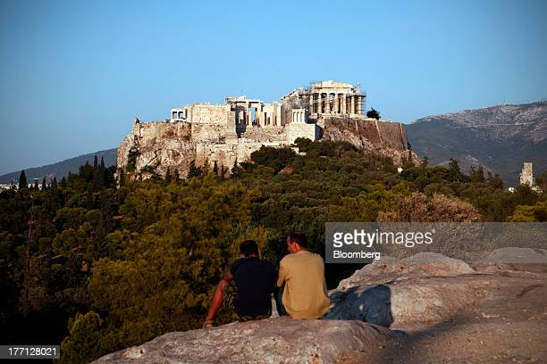 Local men sit on rocks with a view of the Parthenon temple on Acropolis Hill in Athens Greece on Tuesday Aug 20 2013 A third aid program for Greece...