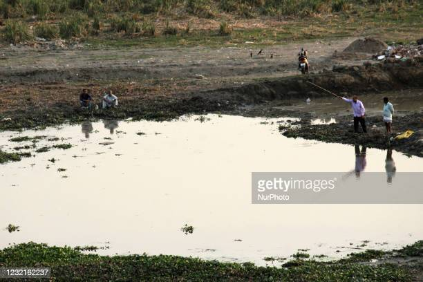 Local men try to catch fish in a pond formed in the floodplain of river Yamuna, in New Delhi, India on April 7, 2021.