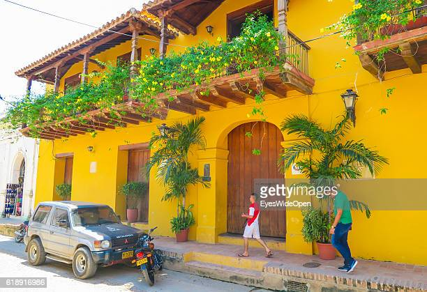 Local men walking by a typical colonial building with plants at the balcony on August 22 2016 in Mompox Colombia The old town is listed by Unesco...