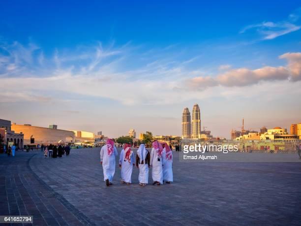 local men walking in Katara wearing Qatar traditional dress, Doha, Qatar