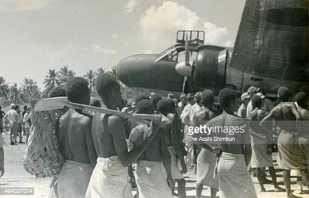 Local men watch an Imperial Japanese Navy fighter aircraft as the airport construction completed circa June 1942 in Kavieng New Ireland Island Papua...