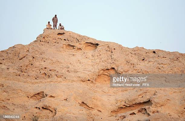 Local men watch the game from a hill top over looking the stadium during the FIFA U-17 World Cup UAE 2013 Quarter Final match between Honduras and...