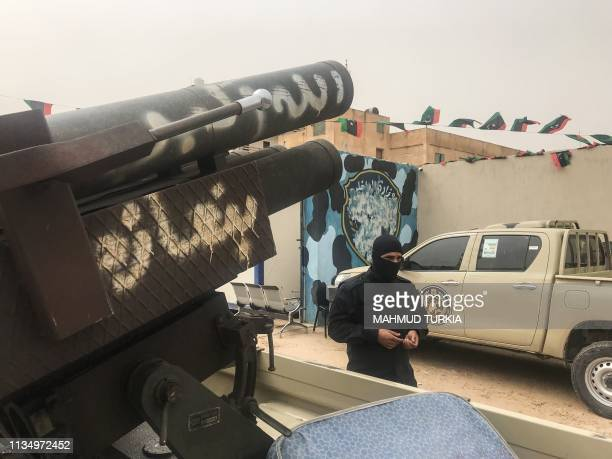 TOPSHOT A local militiaman belonging to a group opposed to Libyan strongman Khalifa Haftar stands next to vehicles the group said they seized from...