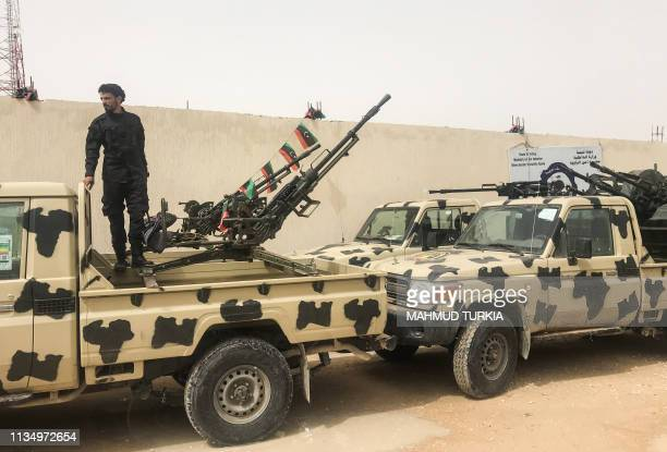 A local militiaman belonging to a group opposed to Libyan strongman Khalifa Haftar stands on an armoured vehicle the group said they seized from...