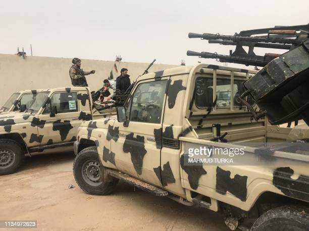 Local militiamen belonging to a group opposed to Libyan strongman Khalifa Haftar stand next to vehicles the group said they seized from Haftar's...