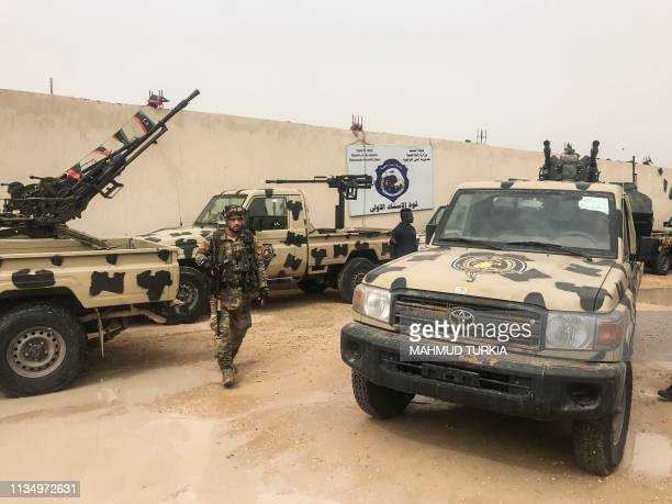 TOPSHOT Local militiamen belonging to a group opposed to Libyan strongman Khalifa Haftar stand next to vehicles the group said they seized from...