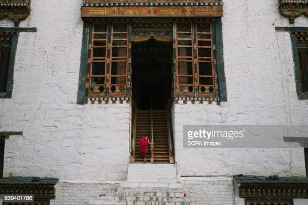 Local monk ascending up the stairs that leads to a monastery.