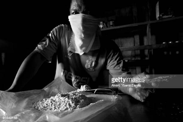 A local narcotics trafficker displaying pure cocaine All the different armed groups who take part in the conflict within Colombia benefit financially...