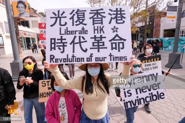 Local natives of Hong Kong participate in a flash mob march to show solidarity with the 47 pro-democracy activists in Hong Kong who were charged for...