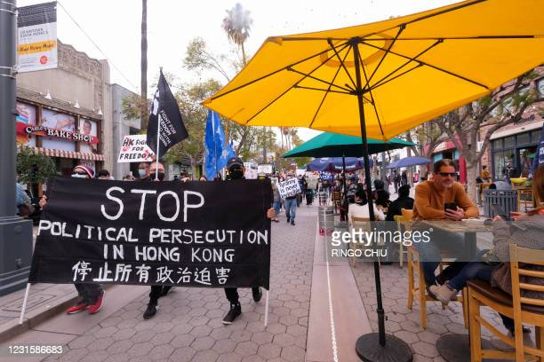 Local natives of Hong Kong pass by outdoor dining area during a flash mob march to show solidarity with the 47 pro-democracy activists in Hong Kong...