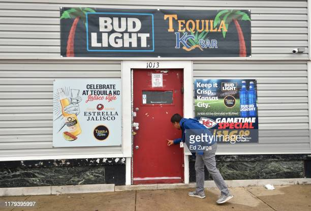 A local news videographer looks at what to appear as a bullet hole in the door entering Tequila KC bar were 9 people were shot and four killed on...