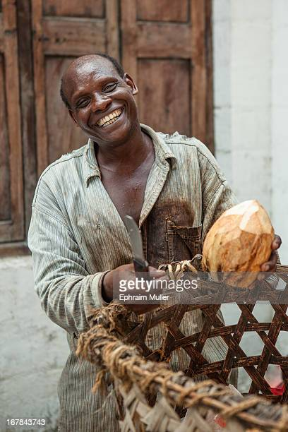 CONTENT] A local of Stonetown wearing a worn stained shirt in Zanzibar with his basket of coconuts poses holding his cutting knife