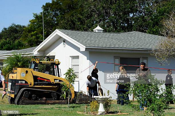 Local officials survey the damage to a residential home partially consumed by a sinkhole on November 14 2013 in Dunedin Florida According to reports...