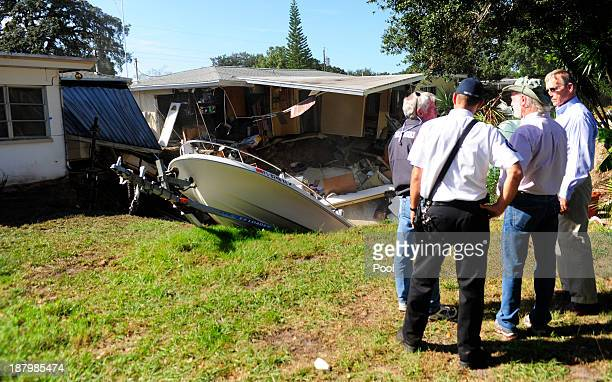 Local officials survey the damage to the rear portion of a residential home that has been consumed by a sinkhole November 14 2013 in Dunedin Florida...