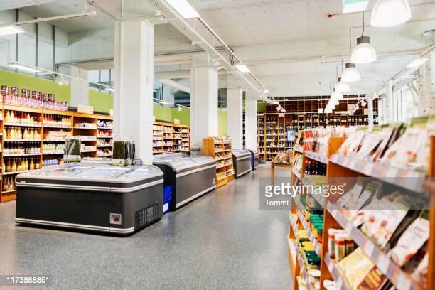 supermercado orgánico local con pasillos y congeladores - mercado espacio de comercio fotografías e imágenes de stock