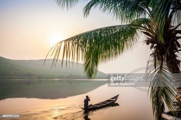 local paddling in wooden canoe, volta river, ghana - ghana stock pictures, royalty-free photos & images