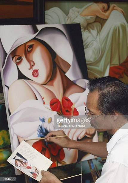 A local painter reproduces by hand High Summer from PolishAmerican art deco painter Tamara de Lempicka at a painting shop in Hanoi 15 August 2003...