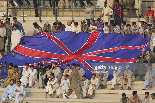Local Pakistan fans display a Union Jack flag during the third day of the First Test Match between Pakistan and England at The Multan Cricket Stadium...
