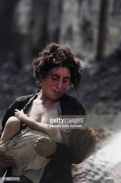 A local Palermo women feeds her baby in the bombed out streets in Palermo Sicily Italy