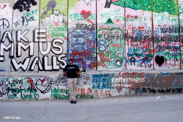 A local Palestinian leaning against the graffiticovered Separation Wall The Israeli Separation Wall is a dividing barrier that separates the West...
