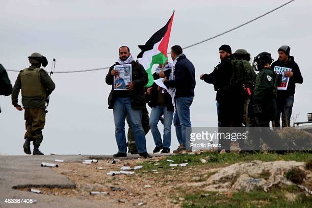 BIL'IN WEST BANK PALESTINE A local Palestinian man holds up a poster of slain ISIS hostage Kayla Mueller who worked in Palestine and was an activist...