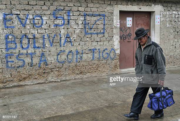 Local passes by a wall with a graffiti supporting Bolivian President Evo Morales for next Sunday's referendum, on August 8, 2008 in El Alto, Bolivia....