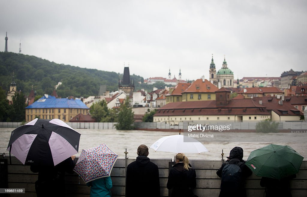 Local people and tourist look over anti-flood barriers near the flooded Vltava River on June 3, 2013 in Prague, Czech Republic. The Czech government has declared a nationwide state of emergency after days of heavy rainfall continue to cause severe flooding. Flood defences have been erected to protect Prague's historic center and people have been evacuated from low-lying areas. At least four people are feared to have been killed and several are missing as rivers continue to rise throughout many regions in Bohemia.