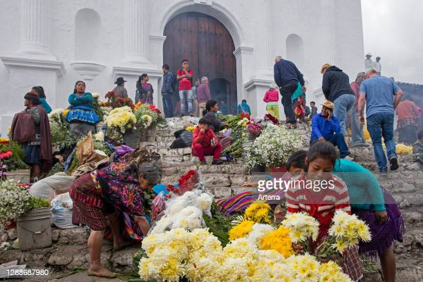 Local people called Mayan K'iche selling flowers on market day in front of the church Iglesia de Santo Tomas in Chichicastenango, El Quiche,...