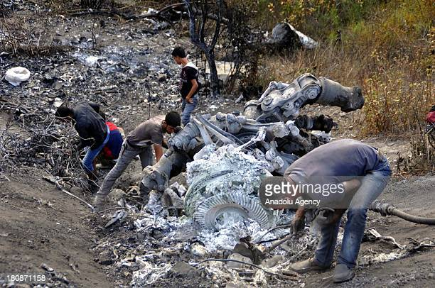 Local people collect the scrap parts from the wreckage of the Syrian helicopter on September 17 2013 in Idlib Syria The wreckage of the PI 17...