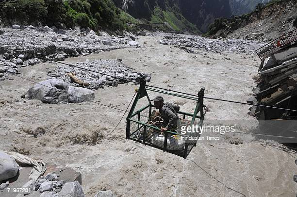 Local people crossing the river Alaknanda in a rope way as the bridge connecting Govind Ghat with the road to Hemkund Sahib Gurudwara is washed away...