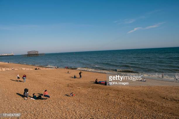 Local people enjoy the sunny day on the beach in Brighton a seaside resort in the county of East Sussex It is a constituent part of the city of...